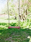 Swing with red painted seat in garden