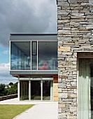 Haus mit Steinmauer und verglastem Anbau