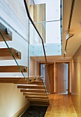 Wooden staircase with glass balustrade