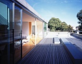 Roof terrace with wooden decking and sliding glass door leading to living room