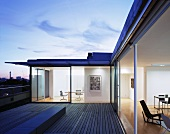 Roof terrace at dusk with view into living room and office