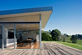 House with glass wall leading to wooden terrace