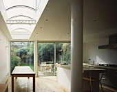 Kitchen with skylight and glass wall leading to terrace