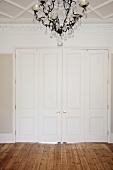 Wide hallway with chandelier, white double doors and wooden floor