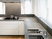 Kitchen corner unit with grey stone work surface and integrated sink