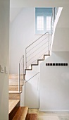 White-painted stairwell with wooden stairs and stainless steel balustrade