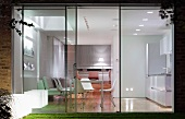Floor-to-ceiling glass wall with view of dining area in illuminated interior