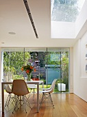 Table with white shell chairs in front of glass wall leading to terrace and beneath skylight in modern dining room