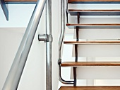 Detail of staircase with wooden treads and stainless steel balustrade