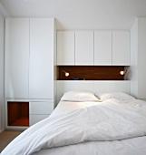 Schlafzimmer mit Doppelbett vor weißem Einbauschrank im Designerstil