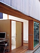 Modern house with open folding terrace door and view of wooden, cubist bathroom installation