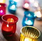 Colourful tea light holders on table