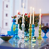 Colourful candlesticks on table with burning white candles