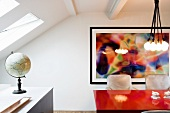 Red dining table in front of painting and globe in front of skylight