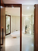 View through open wood and glass door into white designer bathroom