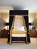 Elegant four-poster bed with black velvet canopy