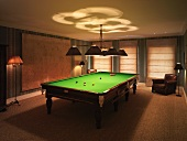 Darkened billiard room with two leather armchairs