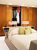 Bedside lamps on head of double bed in front of wooden fitted wardrobes with open door
