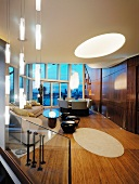 Penthouse apartment with tasteful living room furnishings and oval skylight in ceiling