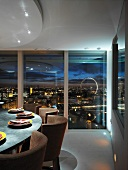 Set dining table in front of floor-to-ceiling glass wall and view of city lights