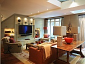 Upholstered seating in front of made-to-measure living room cupboards with flat-screen TV