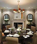 Upholstered chairs around festive, set table in traditional dining room