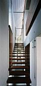 Moderne Treppe mit Holzstufen im schmalen Treppenhaus
