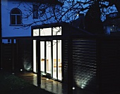 Modern, wooden extension at dusk with illuminated interior