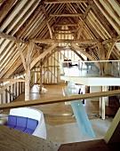 Schräge, moderne Einbauten in historischer Dachkonstruktion - abgehängte Galerieebene mit transparenter Glasbrüstung