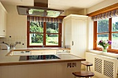 Views of trees through windows in modern country-style kitchen - mix of white-painted and natural wood