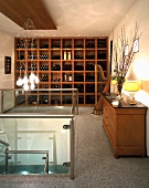 Harp in front of wooden wine rack contrasting with modern steel and glass staircase and contemporary, designer light fitting