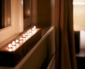 Unfocused atmospheric picture - wooden block with burning tea lights inserted