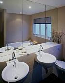 Round washbasins beneath large mirror in modern bathroom