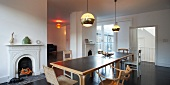 Period flair in London attic flat with long, modern dining table, collection of chairs and retro lamps