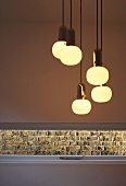 Lit retro light fittings above slit window with view of brick wall