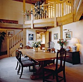 Double-height dining room with rustic wooden staircase and gallery