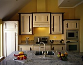 Decorative cupboard doors and granite work surfaces in modern fitted kitchen