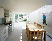 Modern kitchen-dining room with long table beneath skylight