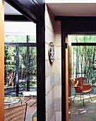 Modern house - view past unrendered concrete block walls with black wooden frames to bamboo garden