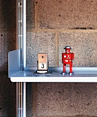 A Playmobil figure next to a retro day calendar on an aluminium shelf against a brick wall