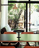 Black platter with pedestal on dining table in open living-dining room with sliding doors leading to garden