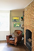 Antique leather armchair next to historic, exposed brick chimney breast