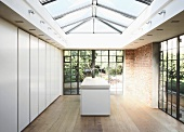 A modern skylight and historic windows in a simple kitchen with walls of handle-less cupboards and an island counter