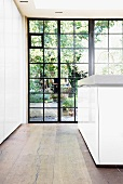 Historic glass wall with metal frame and solid wooden floor in modern kitchen