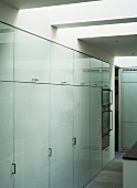 Wall of large, fitted cupboards with white glass doors and bracket handles