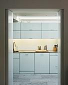weiße, schlichte Einbauküche mit grauem Fliesenboden