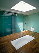 Skylight above sunken bathtub in wooden floor and bluish glass sliding doors in ensuite designer bathroom