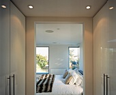 Dressing room with white, glossy fitted wardrobes and open doorway to inviting bedroom