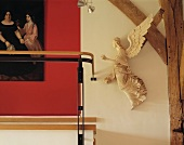 Angel next to half-timbered beams and detail of historic painting against red wall
