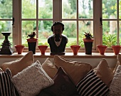 Various scatter cushions in front of windowsill with male bust and pots